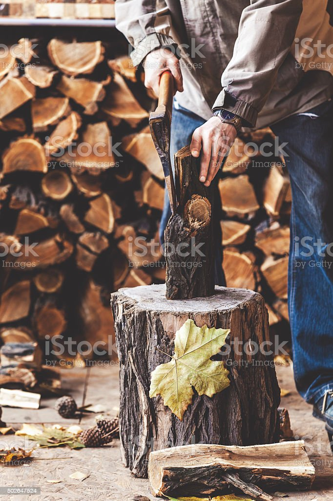 Man chopping wood on stump stock photo