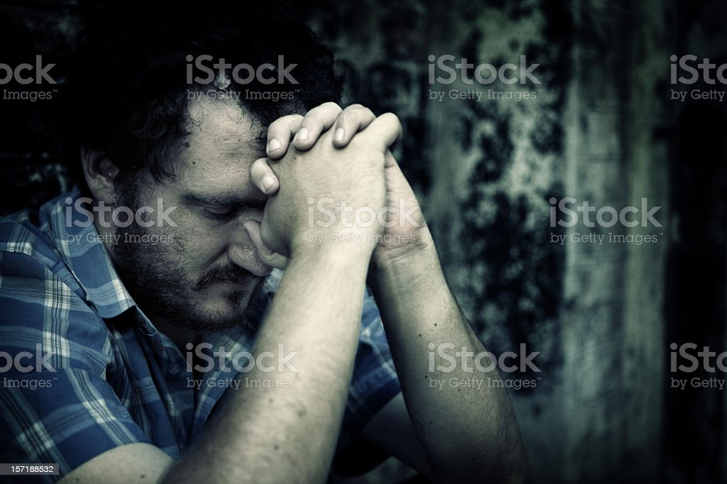 Man clasping hands against forehead in hopeless manner royalty-free stock photo