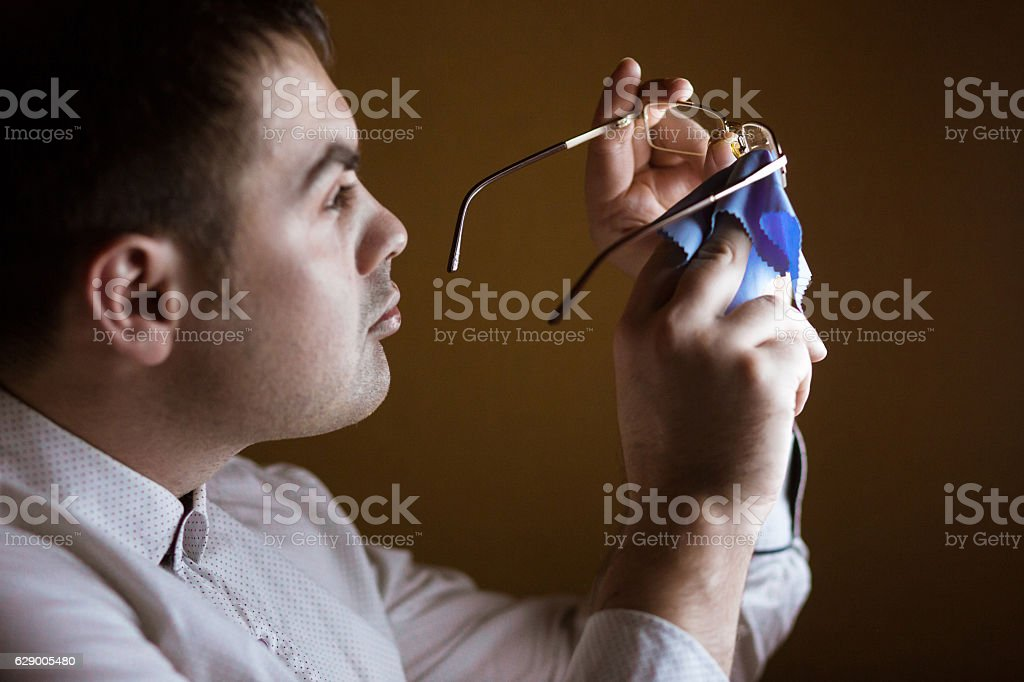 Man cleaning a softie lens of computer glasses stock photo