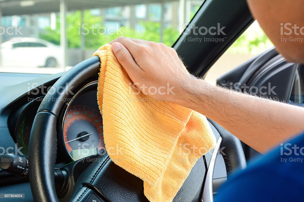 Man cleaning car steering wheel with microfiber cloth stock photo