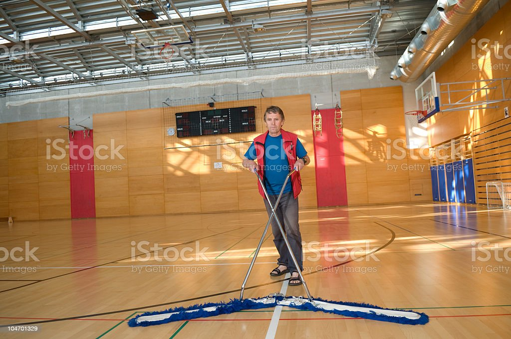 Man Cleaning Floor in Sports Hall royalty-free stock photo