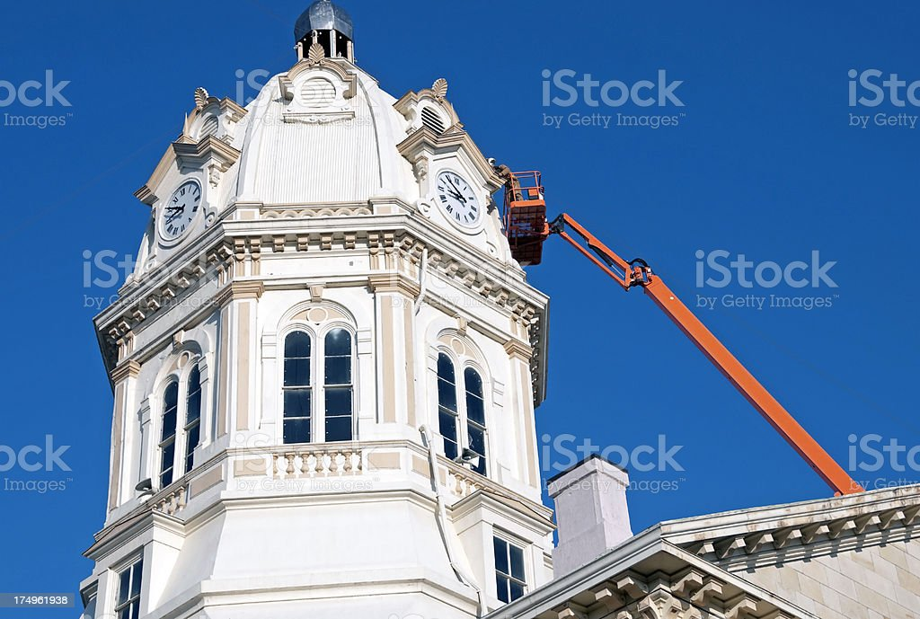 Man cleaning gutters of courthouse clock tower royalty-free stock photo