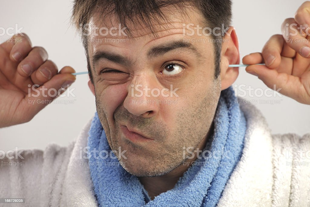 Man cleaning his ears with cotton swab stock photo