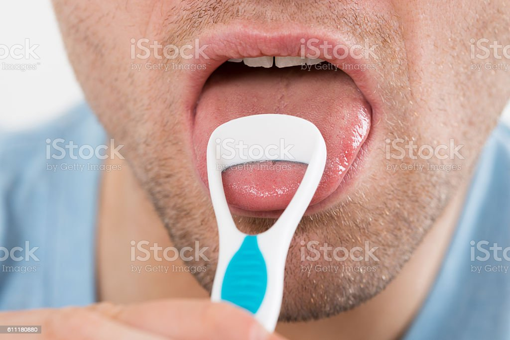 Man Cleaning His Tongue With Scraper stock photo