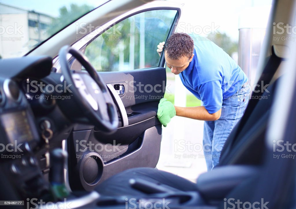 Man cleaning interior of his car. stock photo