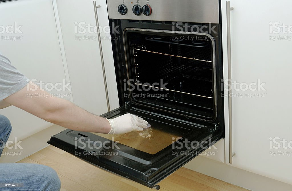 Man cleaning kitchen oven stove door stock photo