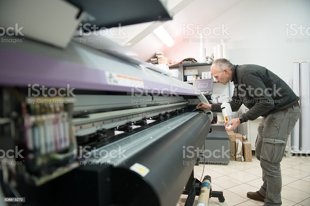 Midlle aged man cleaning large format printer head, small business,...