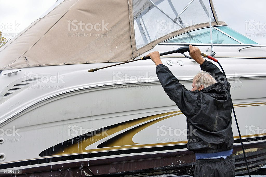 man cleaning power boat stock photo