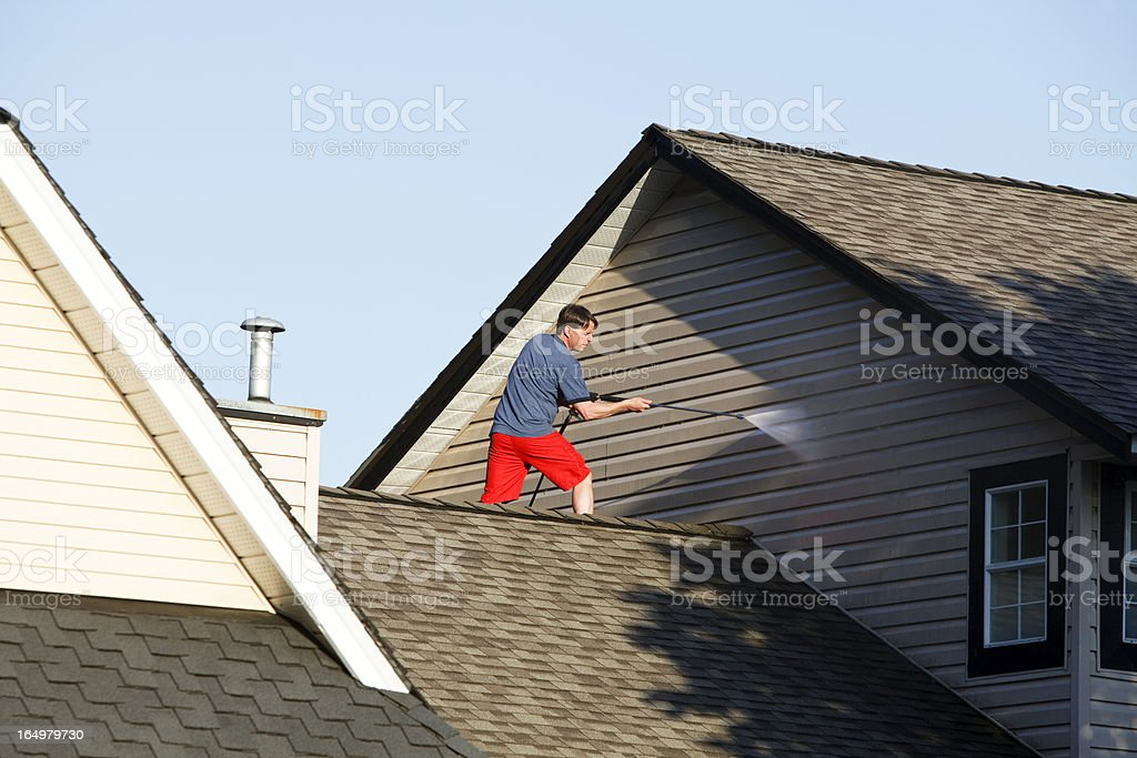 Man cleaning siding on his house with a pressure washer stock photo