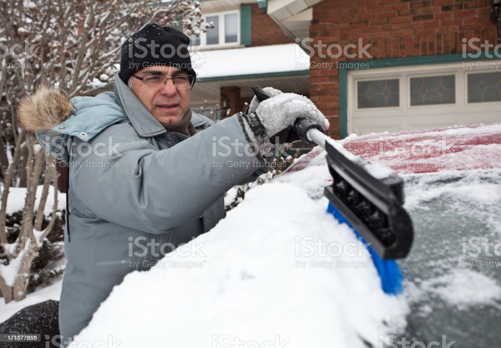 Man Cleaning Snow Off Car stock photo