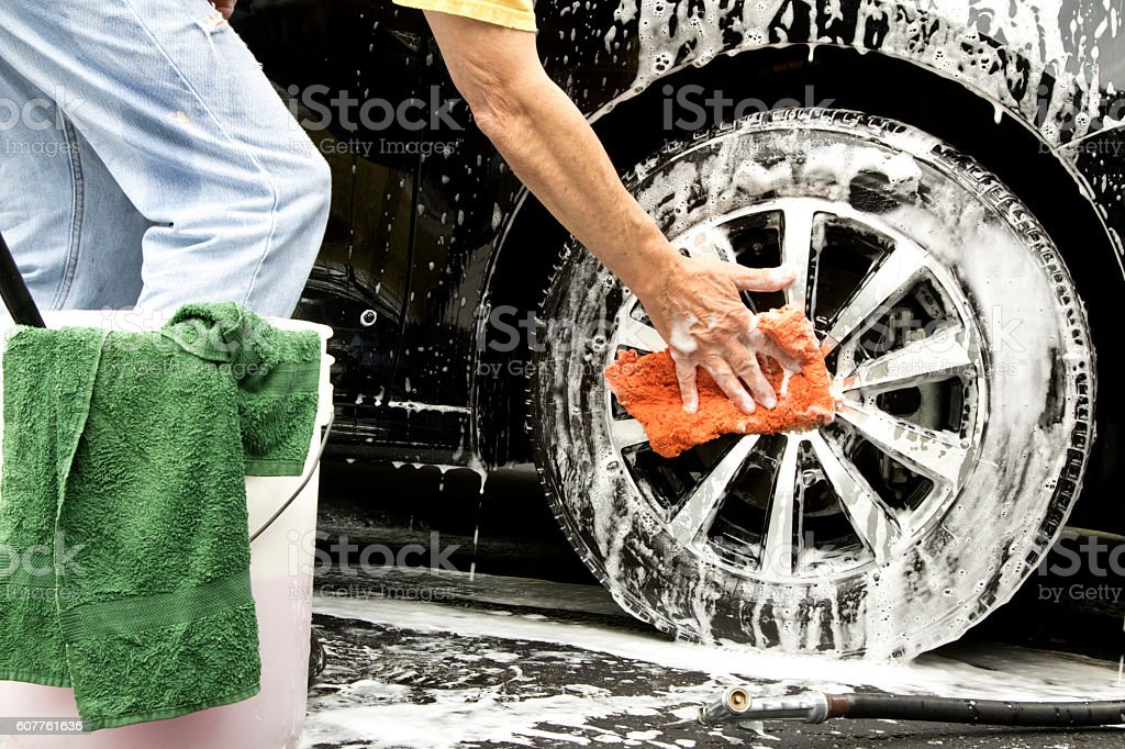 Man cleaning soapy car tire and wheel with sponge stock photo