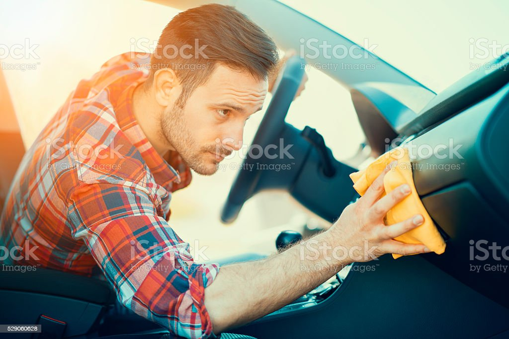 Man cleaning the dashboard of his car stock photo