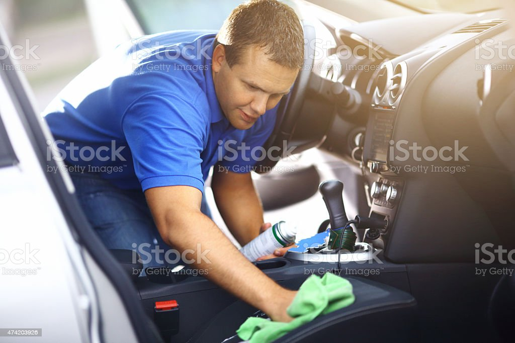 Man cleaning upholstery of his vehicle. stock photo