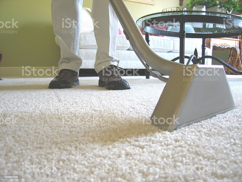 Man cleaning white carpet with industrial vacuum stock photo