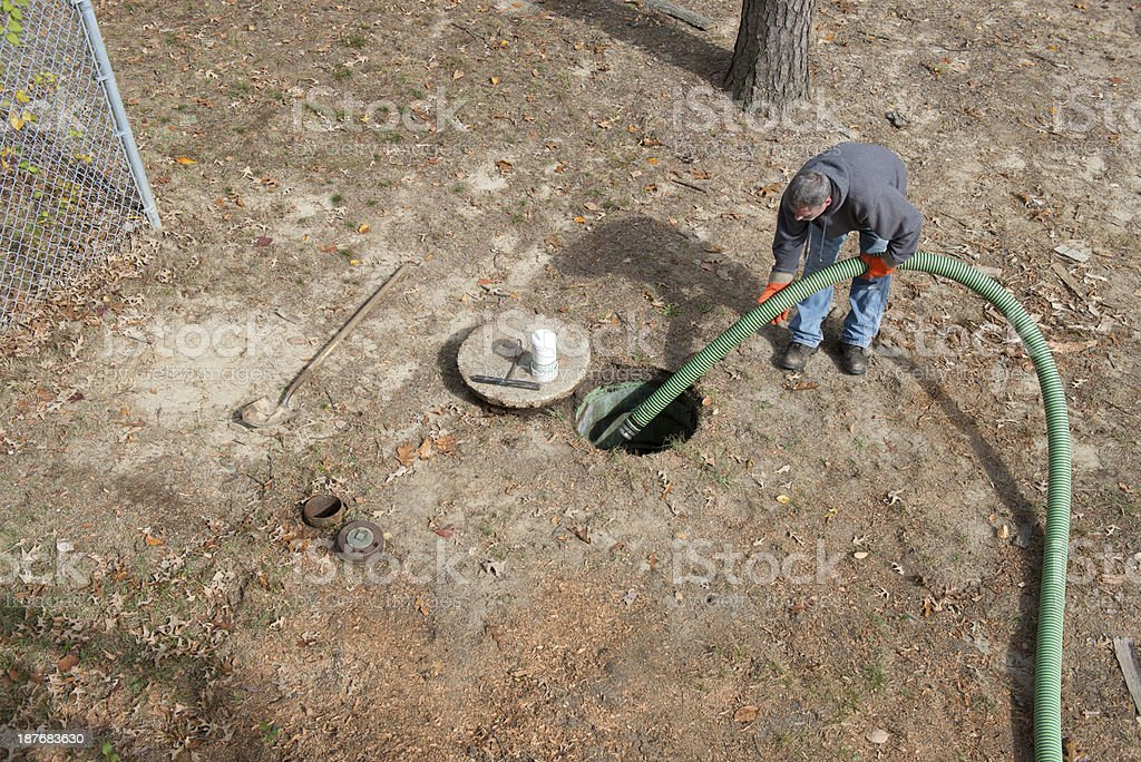 Man Cleans Home Septic Tank stock photo