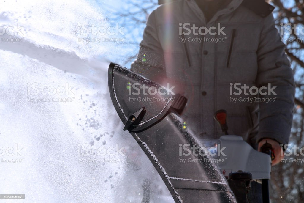 A man cleans snow from sidewalks with snowblower. stock photo
