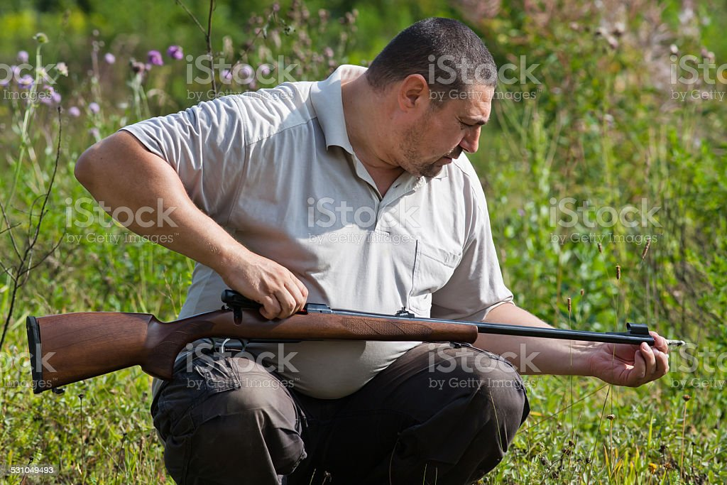 man cleans the barrel of rifle stock photo