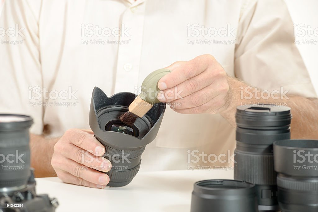 man cleans the lens from accumulated dust stock photo