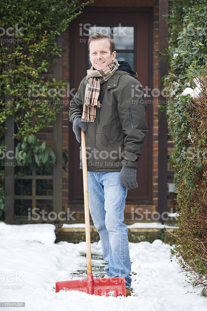 Man Clearing Snow Covered Path Outside Home royalty-free stock photo
