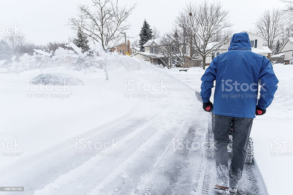 Man Clearing Snow with a Snow Blower stock photo
