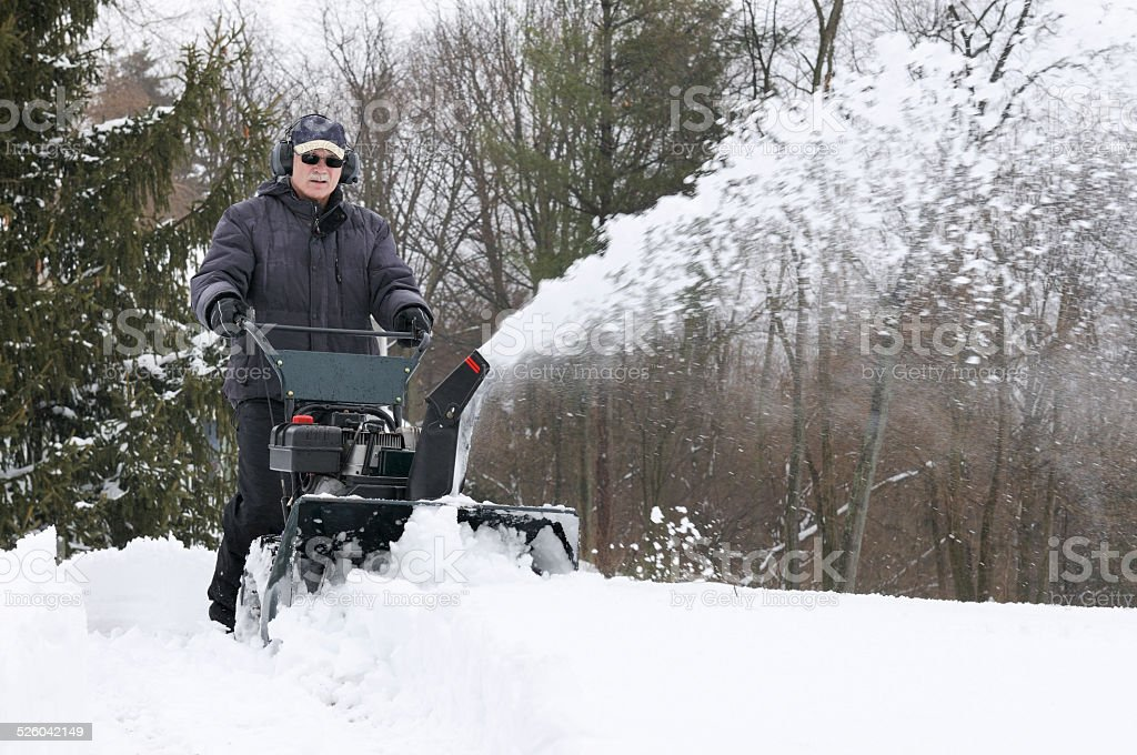 Man Clearing Snow with Snowblower stock photo