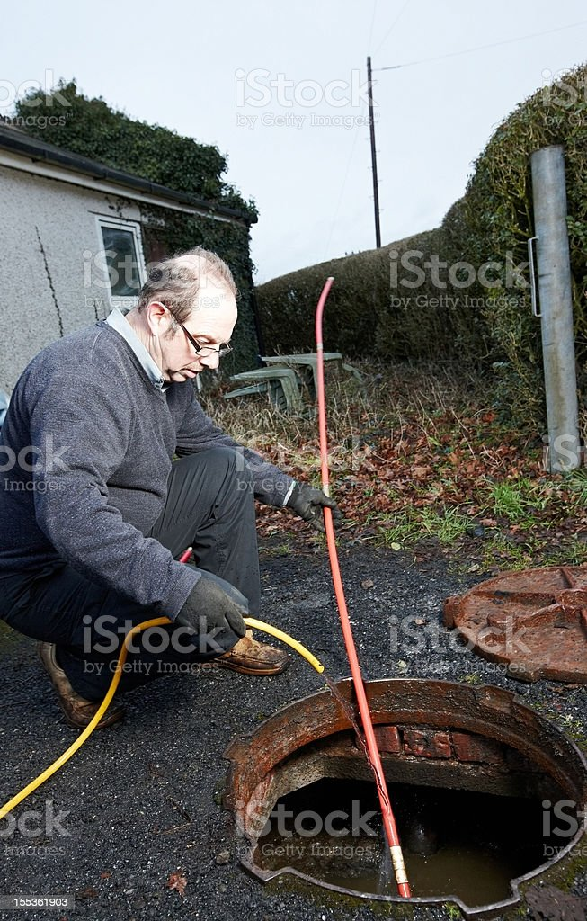 Man clearing the drains stock photo