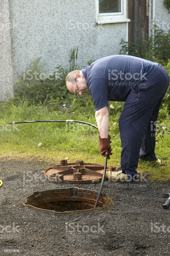 Man clearing the drains royalty-free stock photo