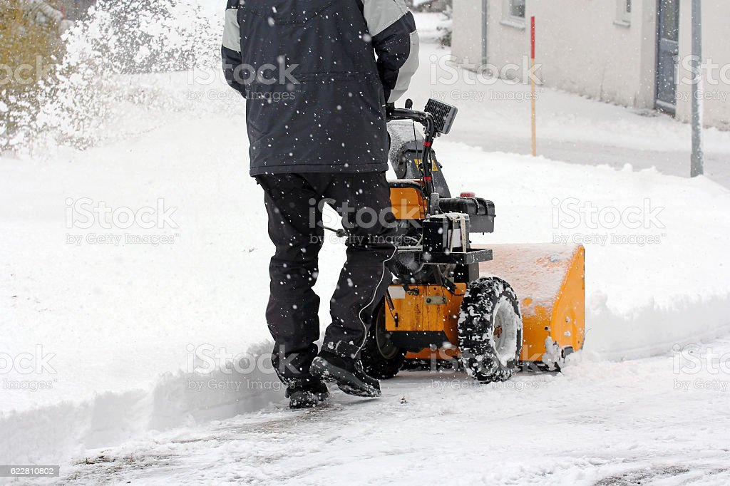 man clears snow with a snow mill stock photo