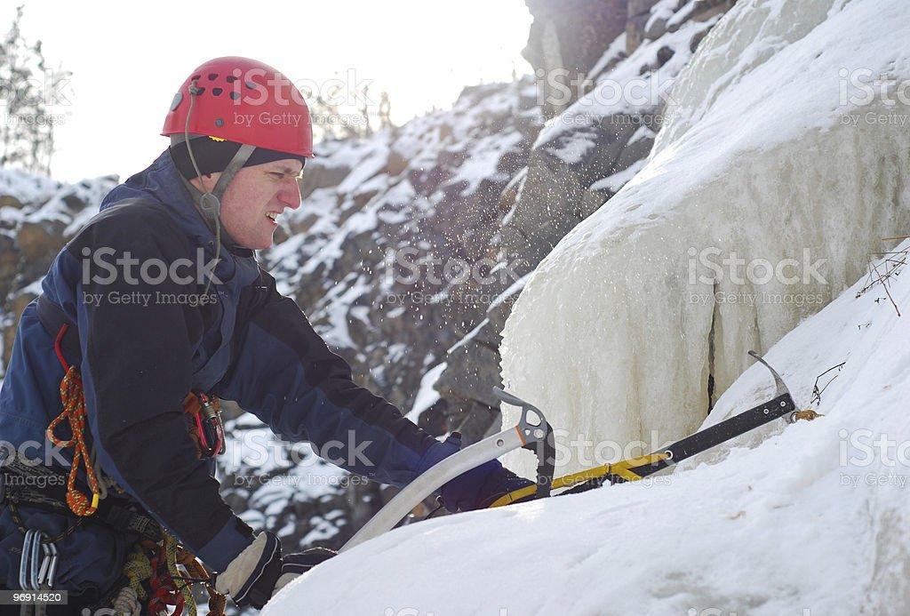 Man climbing a frozen waterfall stock photo