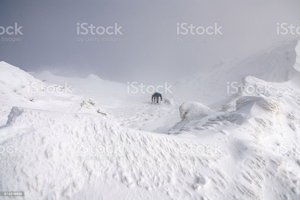Man climbing a glacier coming up out of the clouds stock photo