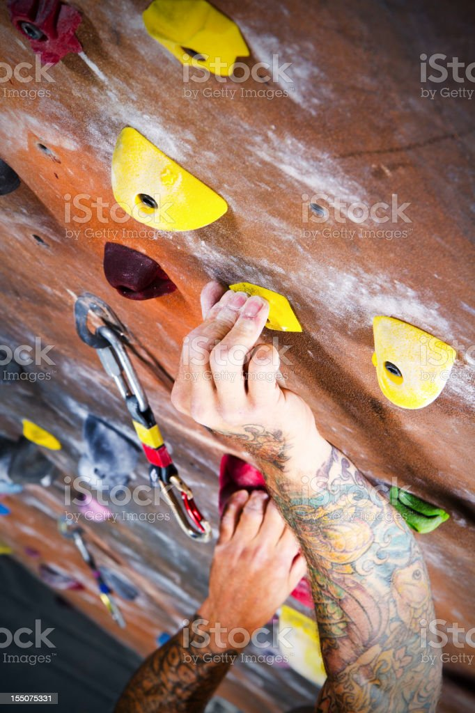 Man Climbing A Rock wall At An Indoor Gym stock photo
