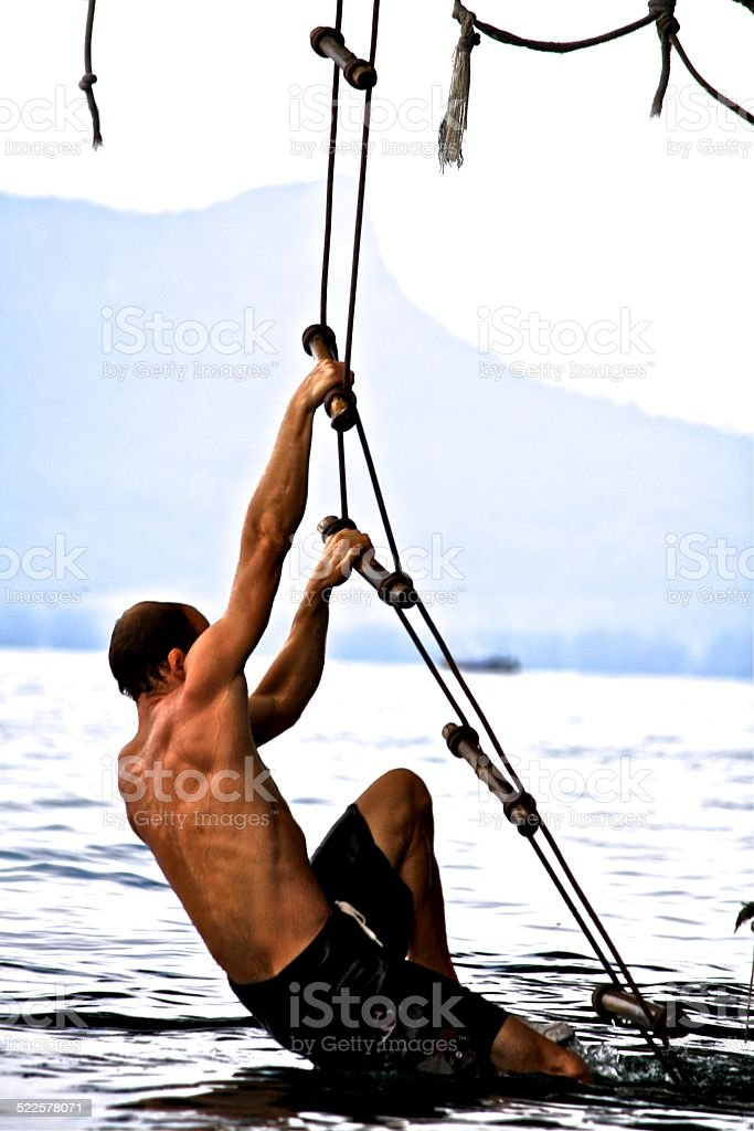 Man Climbing a Rope Ladder Out of Ocean stock photo