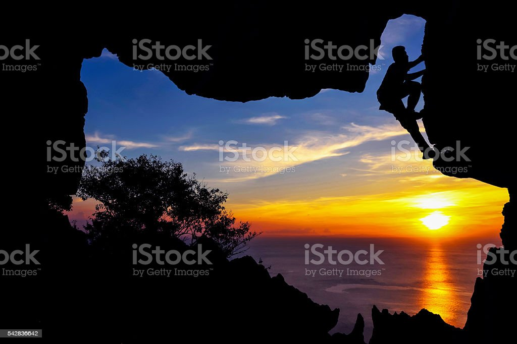 Man climbing cave on the mountain. stock photo