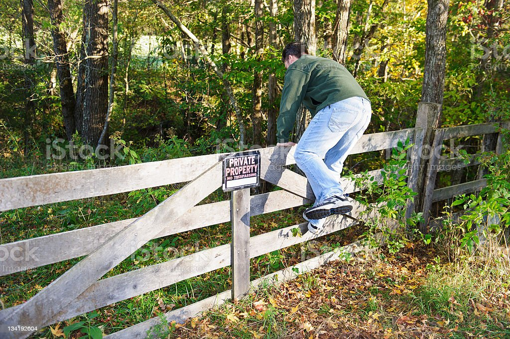 man climbing fence entering posted property stock photo
