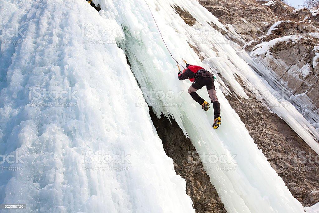 Man climbing frozen waterfall stock photo