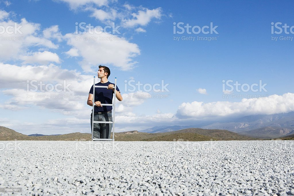 Man climbing ladder outdoors three quarter length royalty-free stock photo