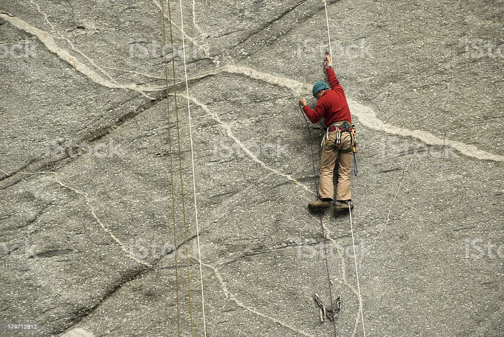 Man climbing on a Granite wall with ropes royalty-free stock photo