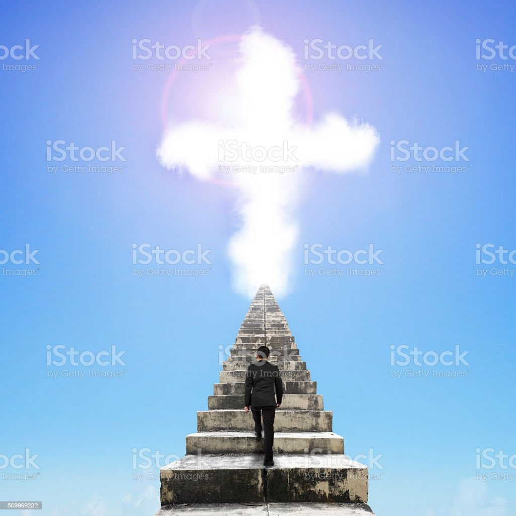 Man climbing on old concrete stairs to cross cloud stock photo