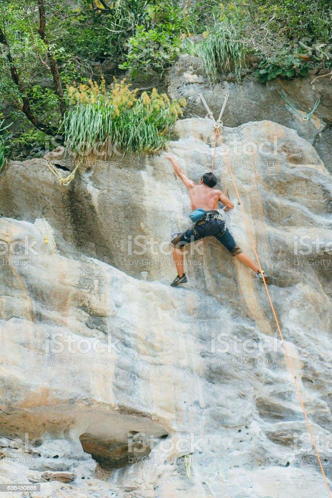 Man climbing on rock stock photo