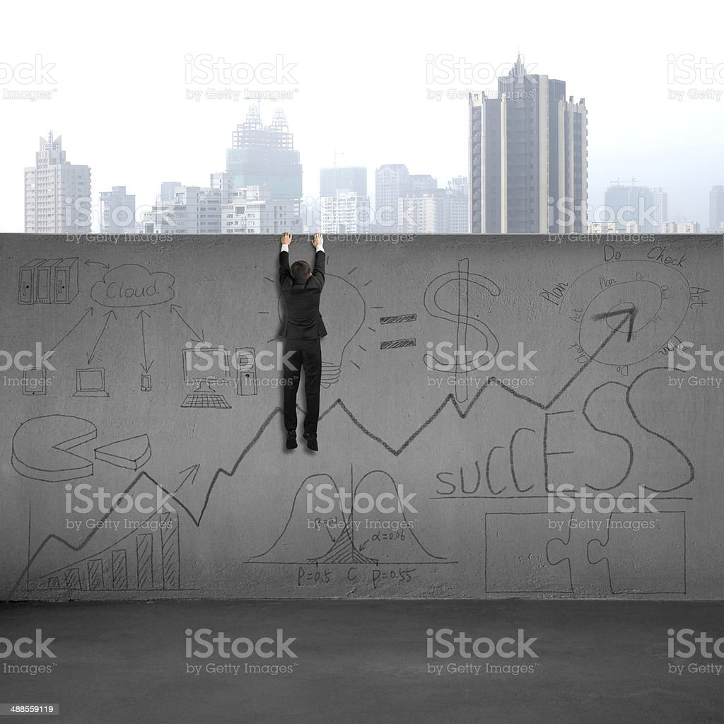 Man climbing over wall with business doodles royalty-free stock photo