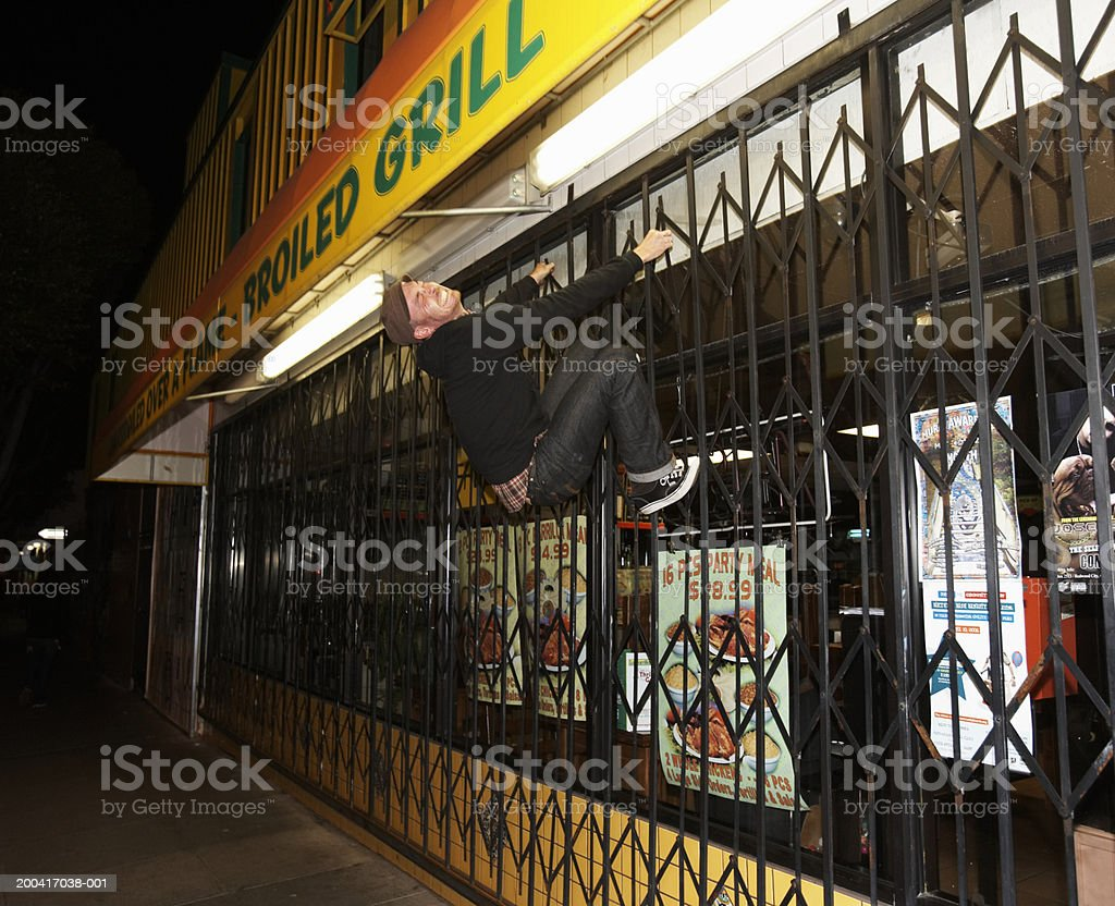 Man climbing security gate in front of restaurant, grimacing, night royalty-free stock photo
