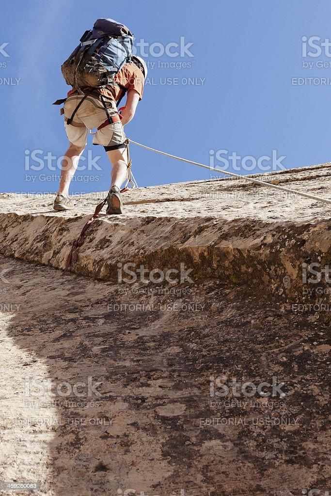 Man climbing up a hill royalty-free stock photo