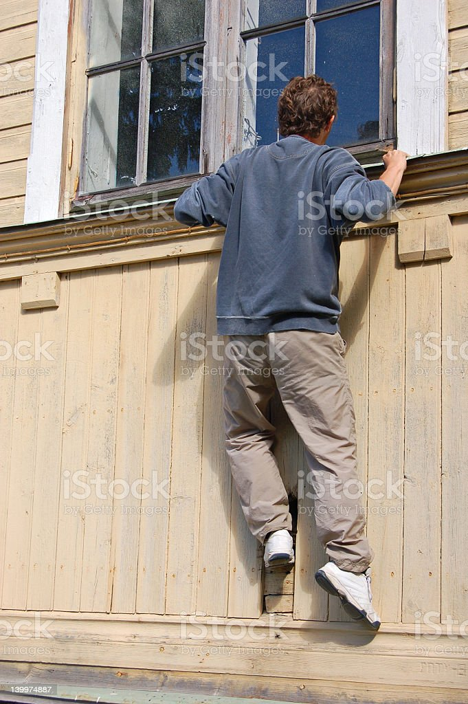 Man climbing up to see through a window stock photo