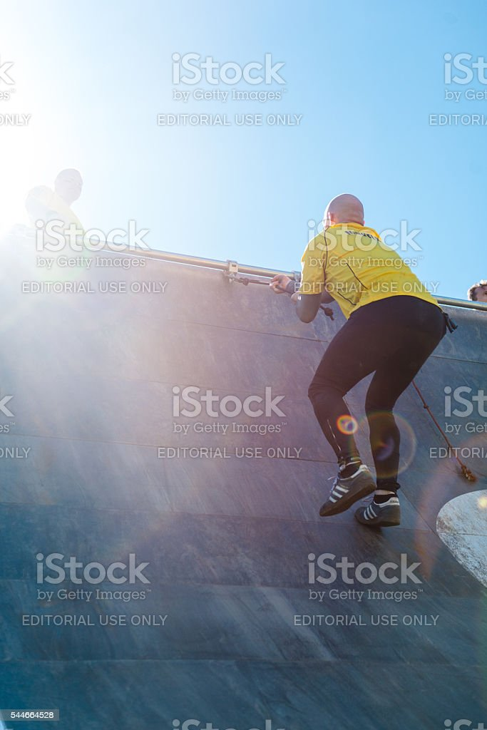 Man climbs over big wall with help from rope stock photo