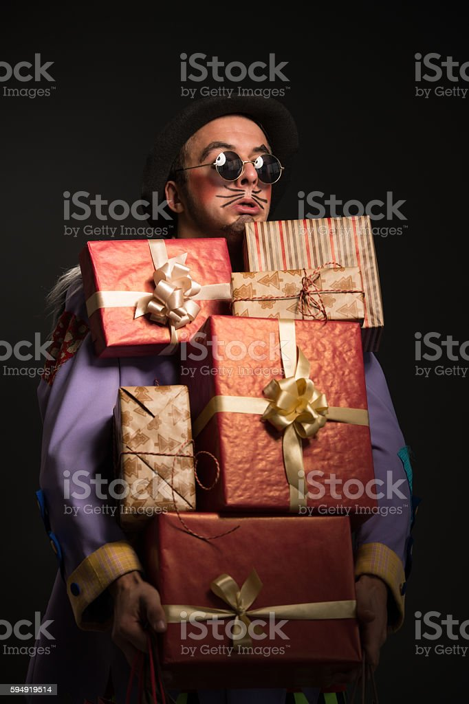 Man clown carrying Christmas gifts stock photo