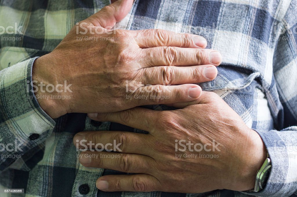 Man clutching his chest stock photo