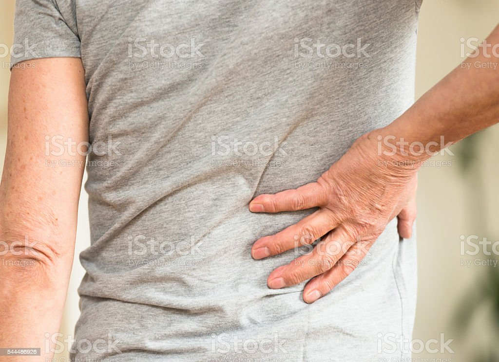 Man clutching his lower back in discomfort stock photo