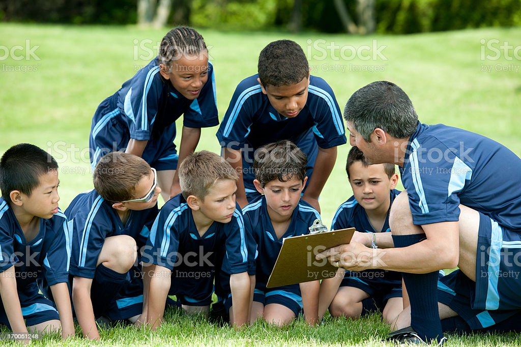 Man coaching youth soccer team of young boys royalty-free stock photo