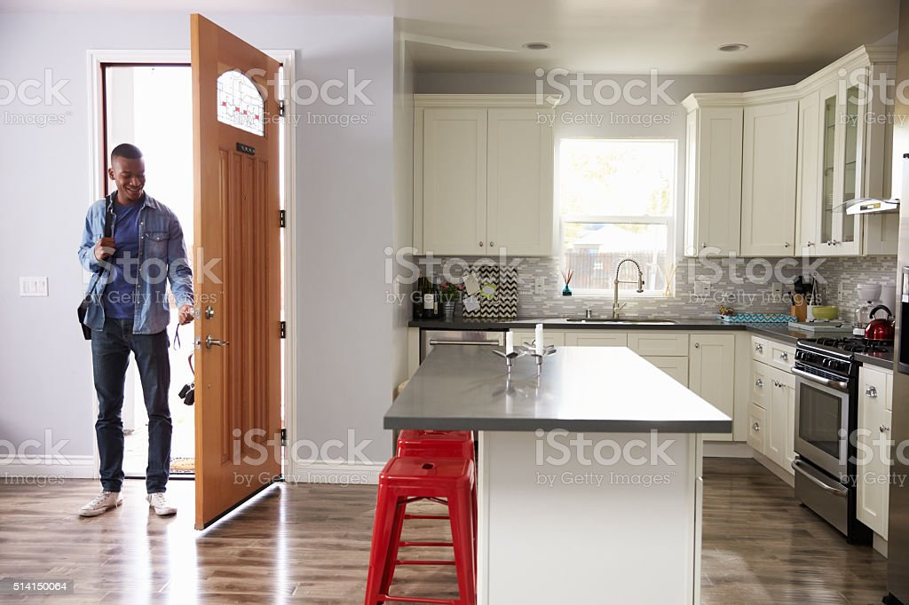 Man Coming Home From Work And Opening Door Of Apartment stock photo