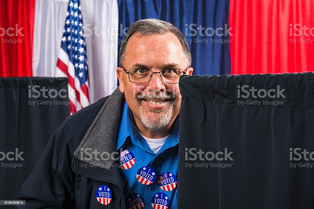 Man committing voter fraud sneaking around voting booths stock photo